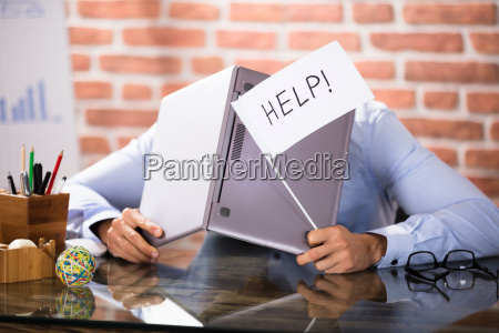 geschaeftsmann der seinen kopf mit laptop