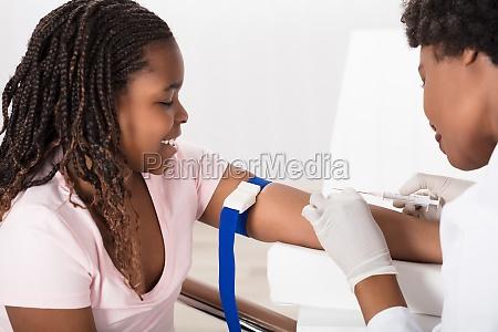 arzt injiziert patient mit spritze um