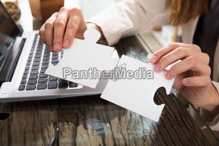 businesswoman holding jigsaw puzzle in office