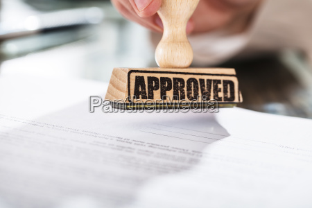 person holding approved stamp on document