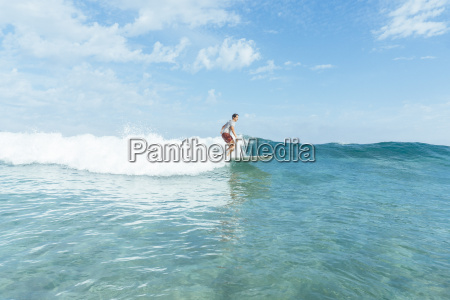 young man surfing crystal clear wave