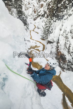 young woman climbing icy wall in