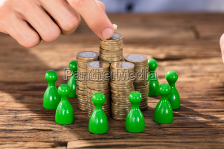 businessman placing coins over stack with