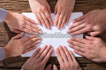 hands touching white paper