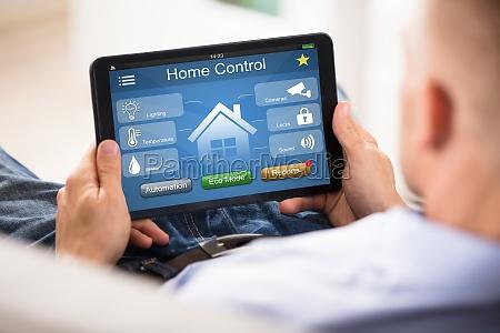 mann mit home control system auf