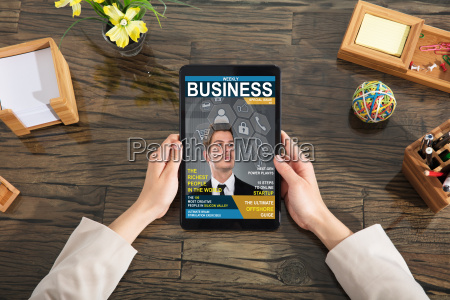 businessperson looking at business magazine