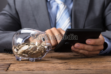 businessman using calculator by glass piggybank