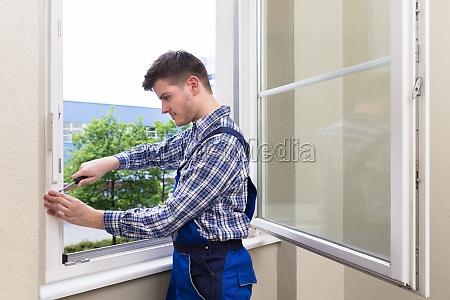 repairman fixing window with screwdriver