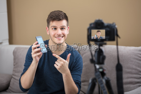 blogger holding mobile phone recording video