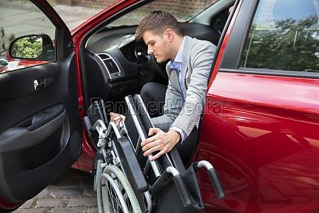 mann sitzt im auto falten sein