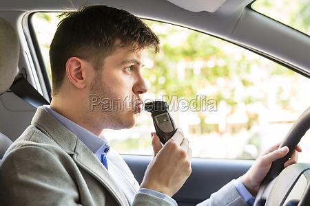 man sitting inside car taking alcohol