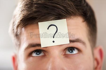 businesspersons stirn mit fragezeichen auf haftnotiz