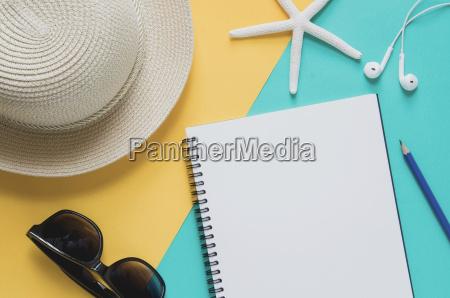 blank notebook mit strohhut sonnenbrille seesterne