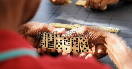 black retired senior man playing domino