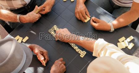 elderly people old men playing domino