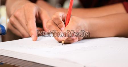 elementary girl doing homework hand writing