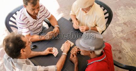 group of senior men playing cards