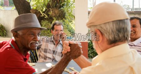 old men shaking hands winning game