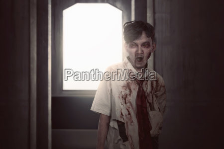 furchtsamer asiatischer zombiemann in der kleidungsstellung