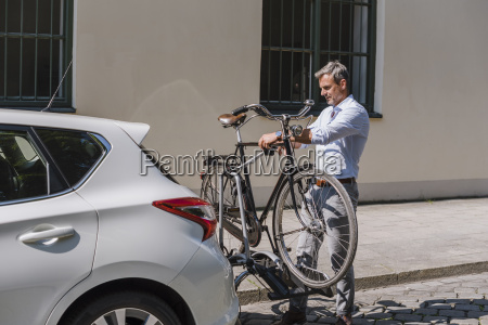 man fixing bicycle on trailer at