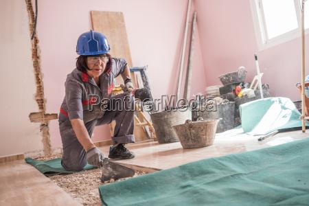senior woman lying tiles at construction