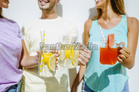 close up of friends holding refreshing