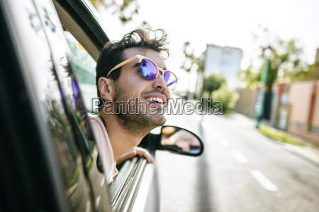 man with sunglasses leaning out the