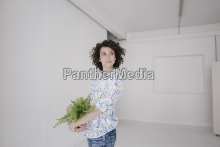 businesswoman holding potted plant