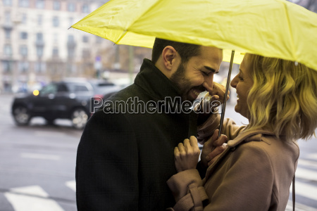 happy business couple under umbrella in