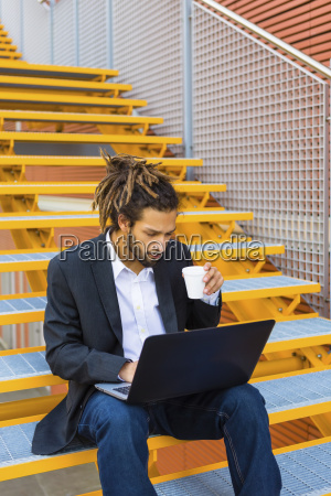 young businessman with dreadlocks sitting on