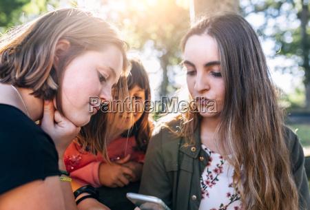 three girls using smartphone outdoors