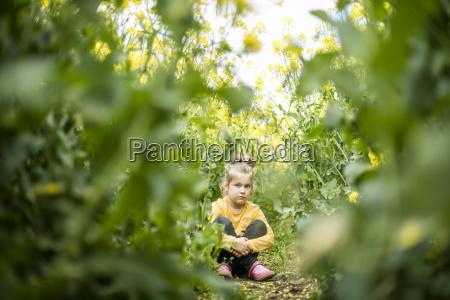 serious girl sitting in rape field