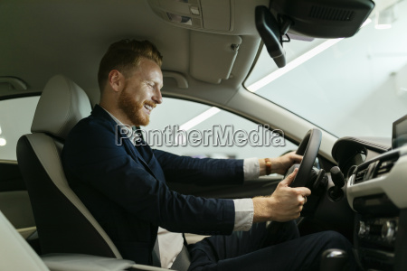businessman testing car in car dealership