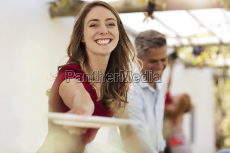smiling woman handing over plate on