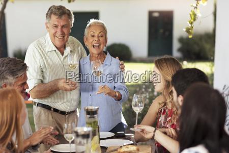 happy senior couple with family having