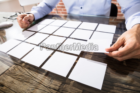 businessman arranging adhesive notes on desk