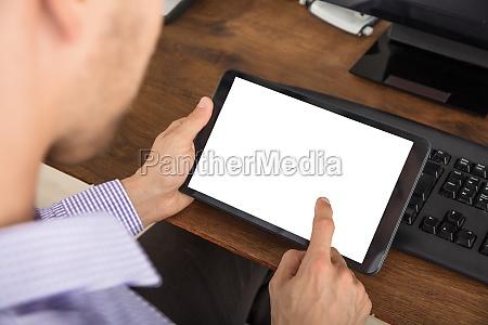 geschaeftsmann nutzt digitales tablet am arbeitsplatz