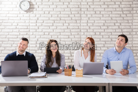 daydreaming businesspeople at desk