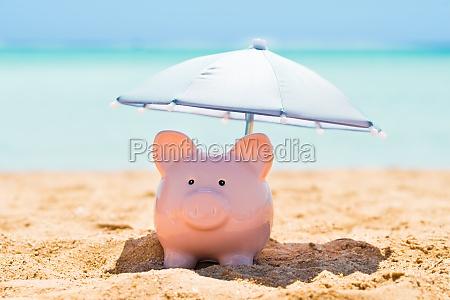 sparschwein unter dem sonnenschirm am strand
