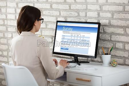 geschaeftsfrau die uebersichtsform auf computer fuellt