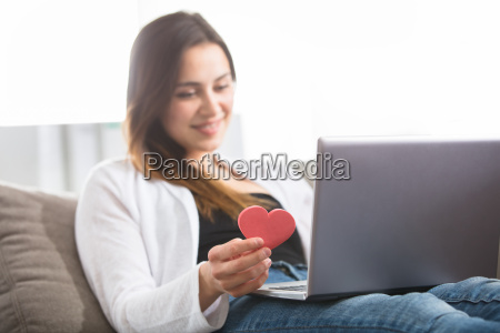 woman holding heart shape using laptop