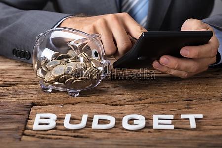 businessman calculating budget by piggybank at