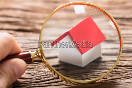 businessman examining model home with magnifying