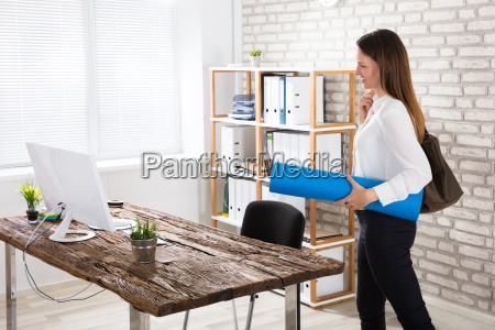 businesswoman walking in office with exercise