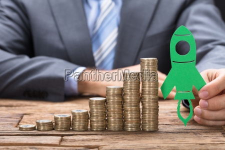 businessman holding green paper rocket on