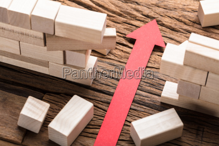 red paper arrow amidst blocks on