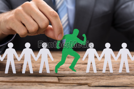 businessman holding green paperman standing out