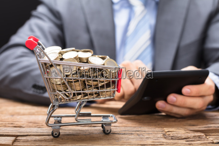 businessman using calculator by shopping cart