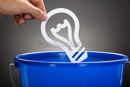 geschaeftsmann wirft papiergluehbirne in blauen eimer