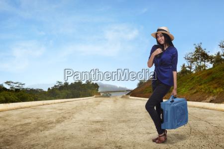 junge asiatische frau touristen haelt koffer